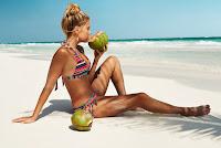 Sylvie van der Vaart wearing a bikini at the beach and holding watermelons