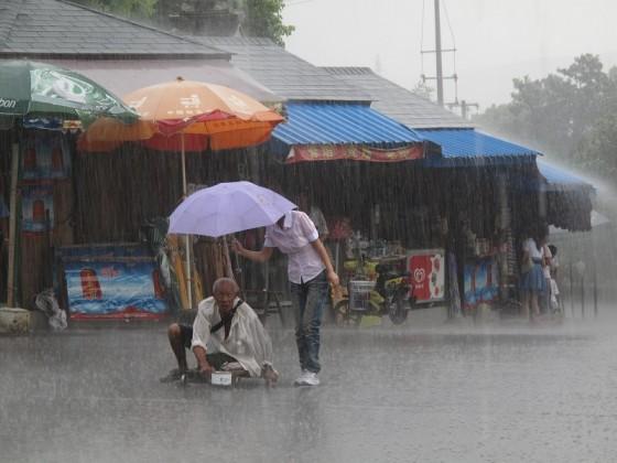 Gadis pegang payung untuk pengemis OKU dalam hujan lebat