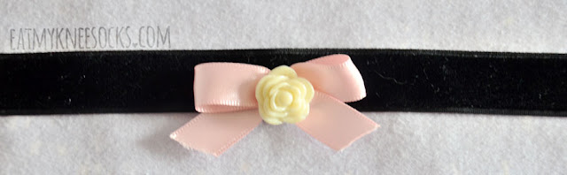 Milkstud's new-collection velvet choker has a cute pastel pink bow-shaped ribbon, along with a cream-colored rose in the center.