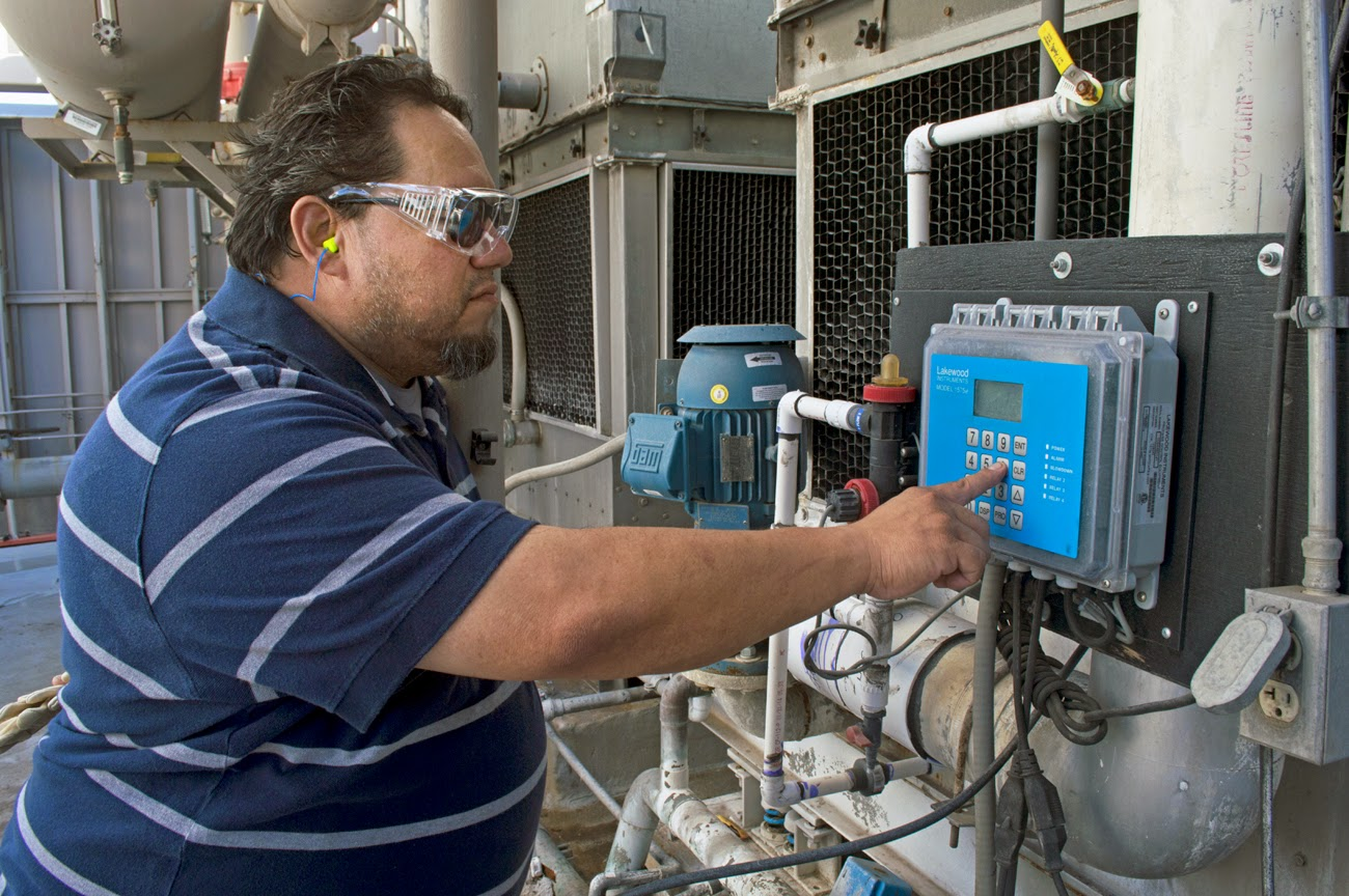 image of a tech reading a guage for a generator