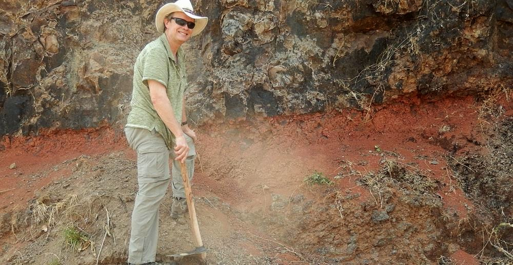 "Mark Richards sampling a weathered zone between two lava flows of the Deccan Traps, near the town of Mahabeleshwar, India. These zones, locally called ""red boles,"" may represent periods of time elapsed between the eruption of successive gigantic lava flows. Credit: Paul Renne"