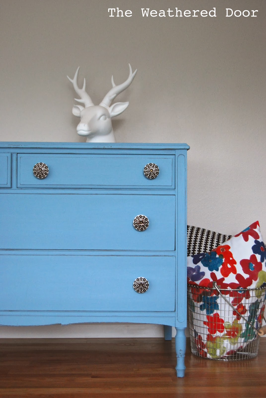 a sky blue dresser with some oversized knobs the weathered door