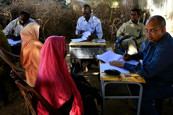 Special Prosecutor for Crimes in Darfur Yasir Ahmed Mohamed (R) and his team talk to women during an investigation  into allegations of mass rape in the village of Tabit, in North Darfur, November 20.