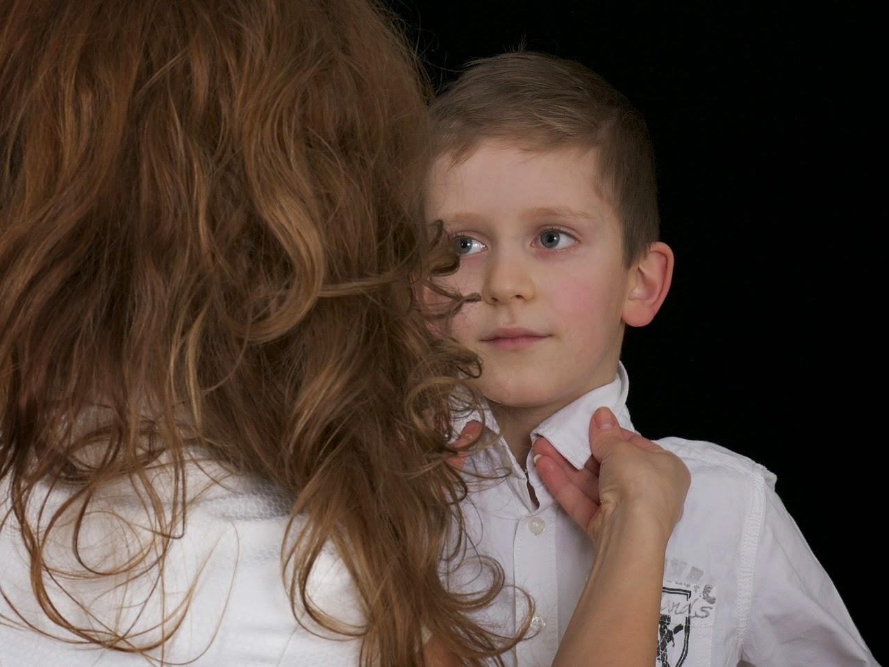 Mutter hilft Kind beim Anziehen