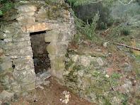 Detall de la porta amb la llinda plana i el mur de reforç de la barraca de vinya de la Vinya Vella de Rubió