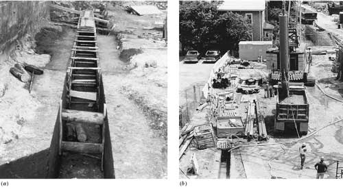 Constructing a slurry wall. (a) The guide walls are formed and poured in a shallow trench. (b) The narrow clamshell bucket  discharges a load of soil into a waiting dump truck. Most of the trench is covered with wood pallets for safety.