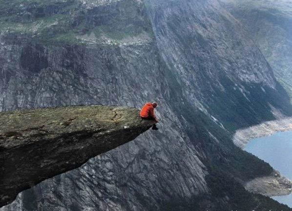 Sad Man Sitting On Cliff