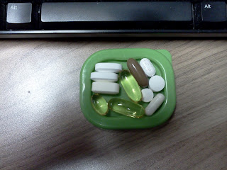 A green dish sitting on a wood desk holding eleven different pills