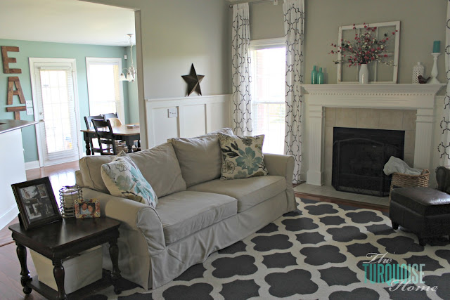 Gorgeous Living Room Makeover with beautiful DIY board and batten, Pottery Barn sofa, stenciled curtains, warm wood and pops of turquoise!