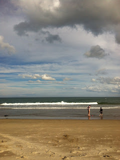 A shot of a beach. Two small children play in the waves.