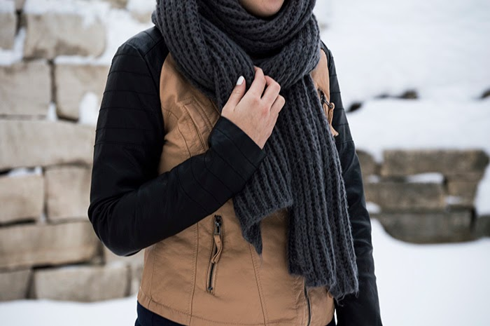 A close up of a gray knit scarf worn with a two toned faux leather jacket.
