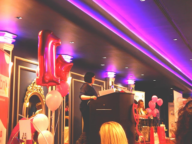 Deirdre standing at a podium surrounded by pink balloons
