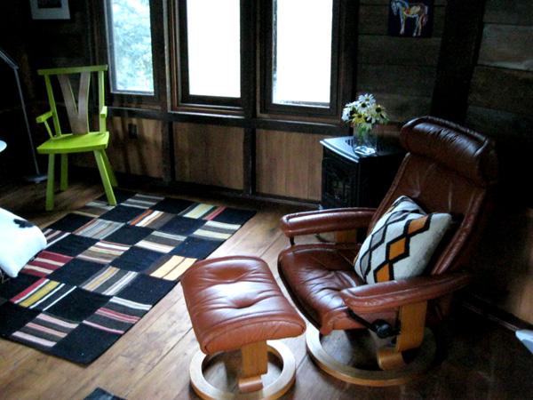 butaca de piel y puf en el interior rustico