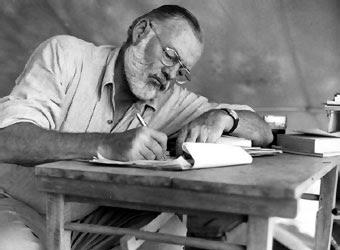 Hemingway sentado escribiendo en una mesa.