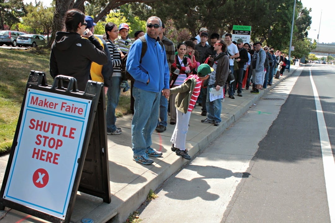 Maker Faire attendees stand in line waiting for the off-site parking shuttle