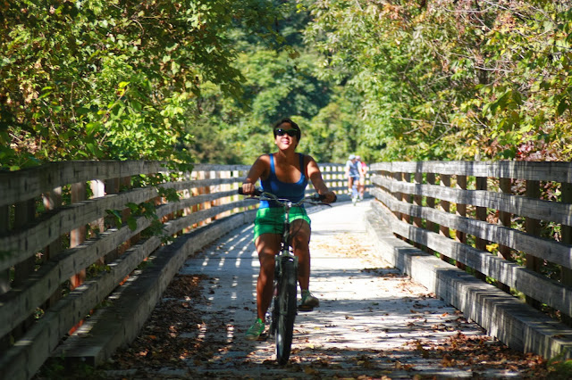 Kristina riding bike on wood bridge