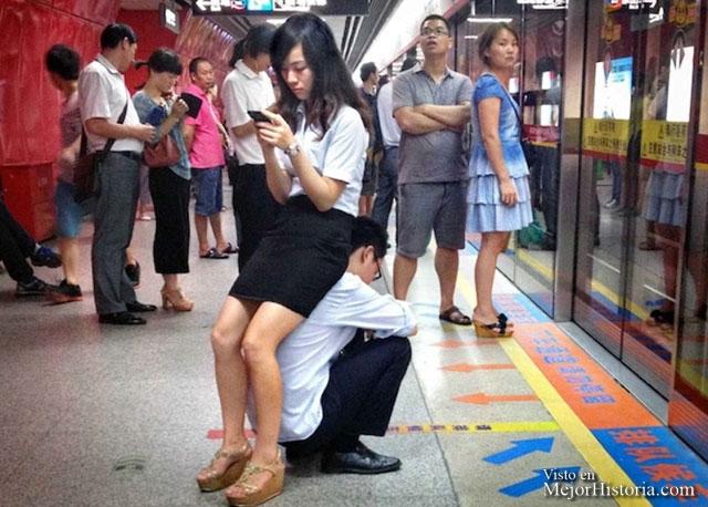 Chico se ofrece como asiento para chica en el metro, mientras ella consulta distraida su teléfono.