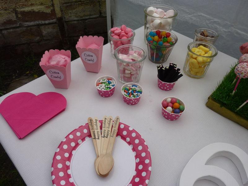 table avec nappe blanche, caissettes et assiettes roses à petits pois blancs
