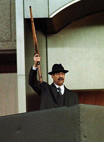 Saddam Hussein dengan senapannya