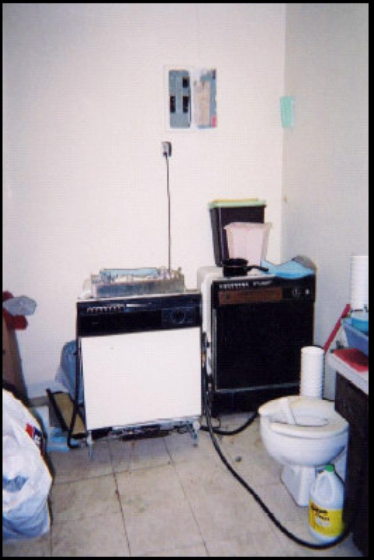 A small, cluttered room with a toilet near a portable dishwasher