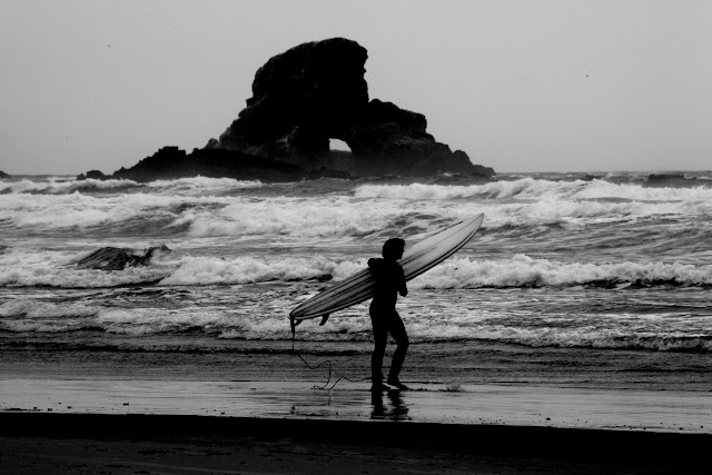 A surfer getting ready to go surfing on the coast of Oregon near Cannon Beach.