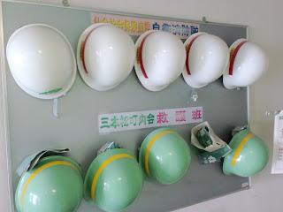 写真:壁にかけられた病院の消防隊と町内会の救護班のヘルメット