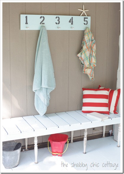 This porch decor is pool ready with a white wooden bench and coastal themed towel rack