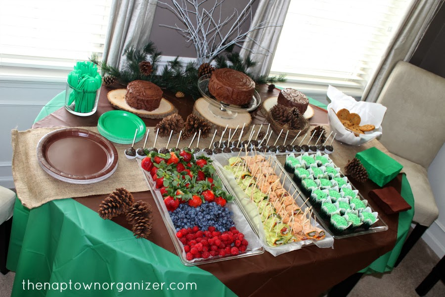woodland birthday party food table - berries, spiral wraps, tree cakes, smash cakes, cupcakes, cookies