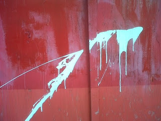 A red door with a streak of white paint splashed across