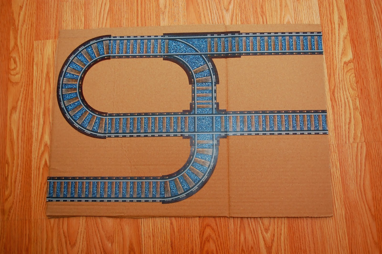printable train tracks glued to second cardboard panel