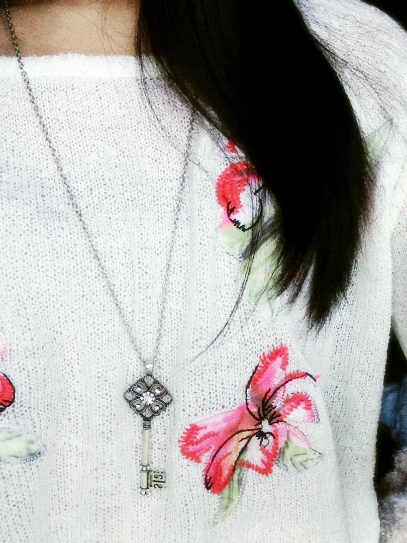 Photo of Born Pretty Store's key necklace when worn. Paired here with a floral sweater from Japanese fashion brand Snidel.