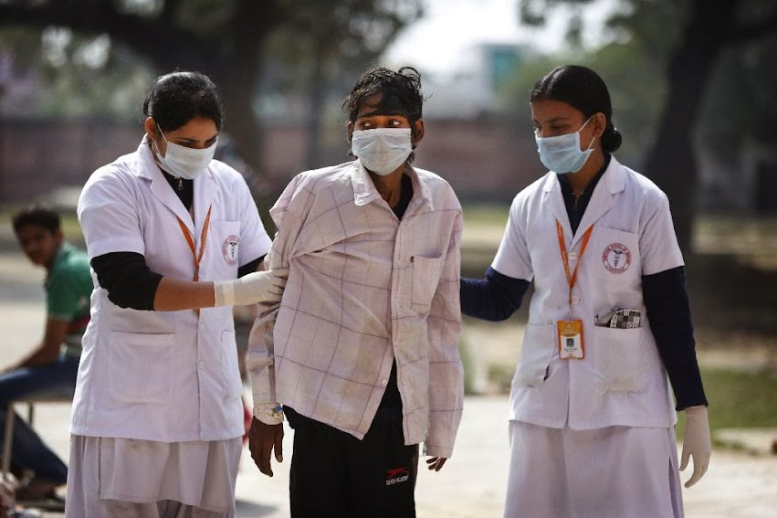 In this Monday, Feb. 3, 2014 photo, Indian nurses help a tuberculosis patient Manjeet Mishra, 18, center, walk towards his ward at Lal Bahadur Shastri Government Hospital at Ram Nagar in Varanasi, India.