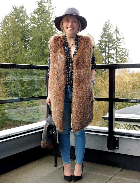 styling blue denim skinnies with pumps, a patterned shirt, long faux-fur vest, and floppy hat