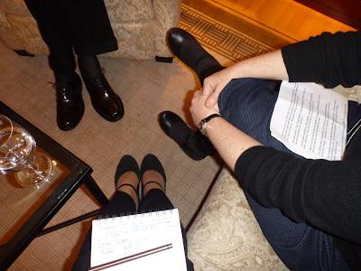 Füße eines Mannes in schwarzen Schuhen mit schwarzen Anzughosenbeinen, Beine einer Frau in blauer Stoffhose mit Fragen auf den Knien, Füße in dunkelgrauer Anzughose mit Notizblock drauf. Angeschnitten ein Couchtisch mit Wasserglas. Teppich und Möbelstoffe von der schweren, eleganten Sorte ...