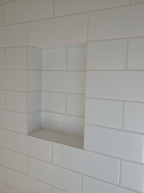 Built in shampoo shelf with gently sloped bottom edge to prevent  title=