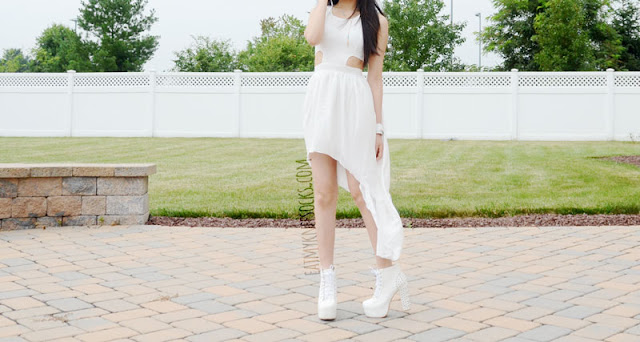 An edgy all-white summer outfit, with a cutout-detailed high-low hem dress and spiked high-heel platform booties.