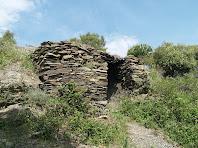 La barraca de Ca l'Onclet adossada al marge rocós