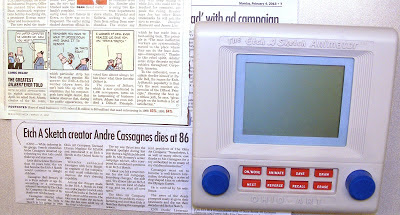 LCD electronic version of the Etch-A-Sketch toy - cartoon of Dilbert telling his boss that he has to turn his laptop upside down and shake it to reboot - newspaper article Etch A-Sketch Creator Andre Cassagnes dies at 86