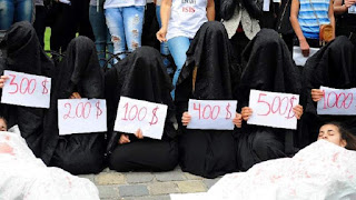 recreation of a slave market in iraq where women in chadors are sold, holding up price tags