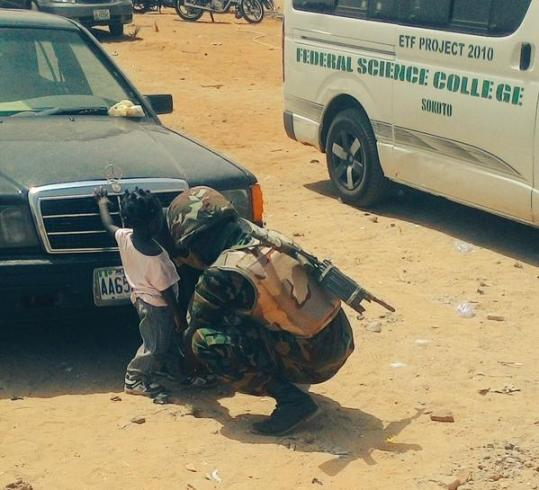 Nigerian soldier helps little girl put on sandals
