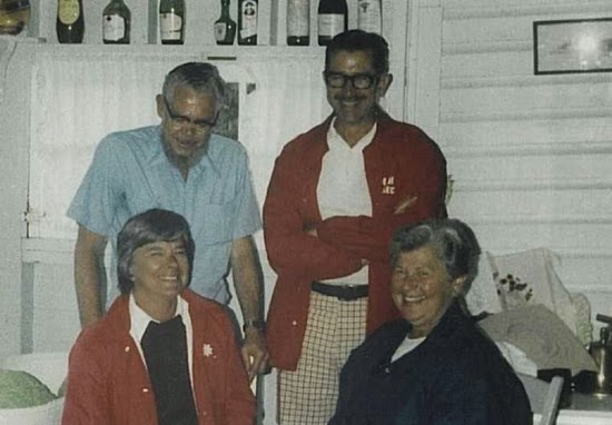 Two adult men standing behind two seated adult women in a posed group photo