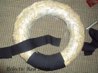 Wrap black strips around straw wreath