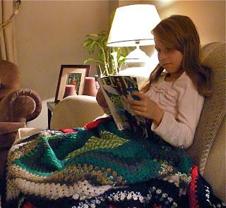 Los niños leen con la manta de abuela hecha a ganchillo