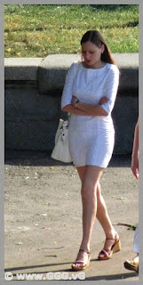 Slender young woman in tight white summer dress