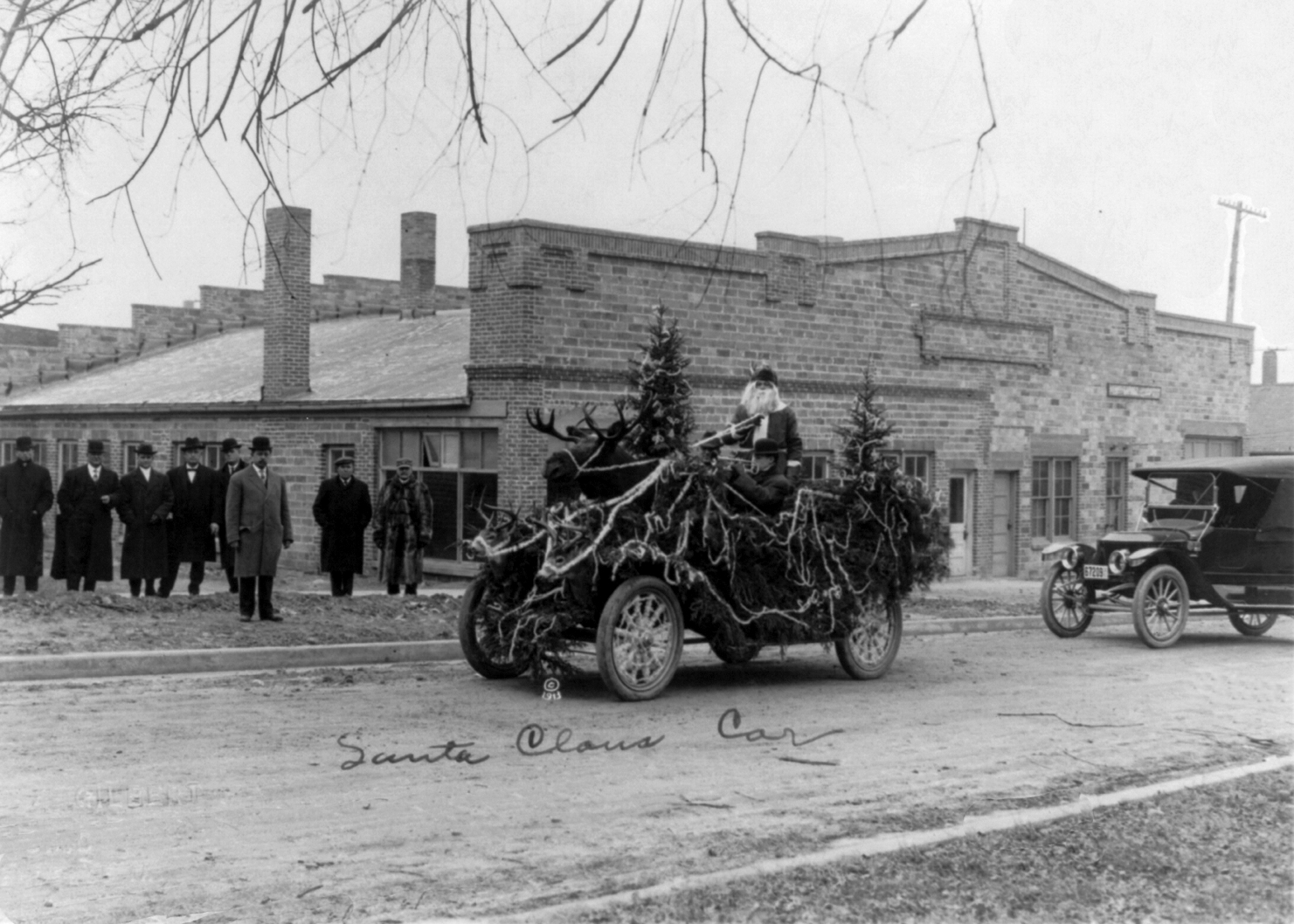 Santa Claus in automobile decorated with Christmas trees, moose and deer heads