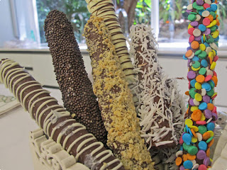 Palitos com chocolate derretido e confeitos