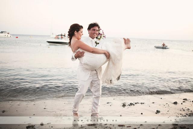 novio descalzo coge en brazos a la novia en la orilla del mar