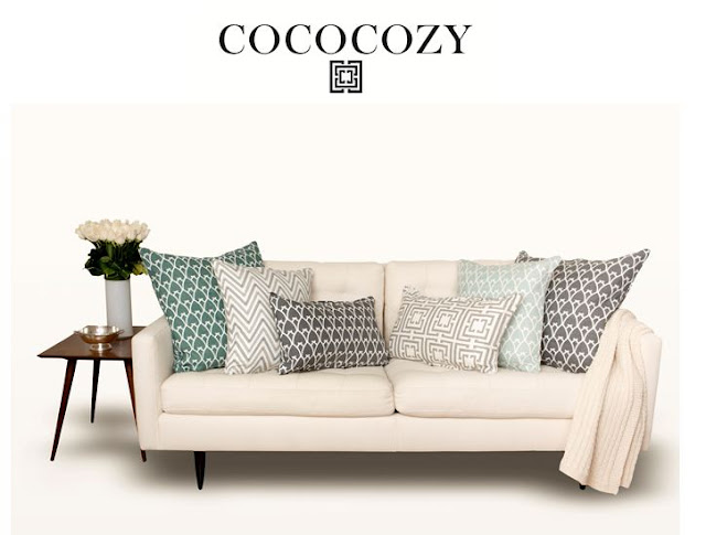 Sofa with gray and sea green pillows and roses