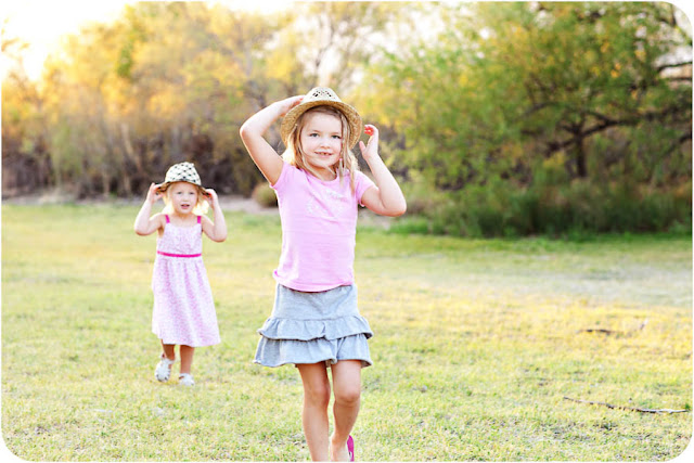 Little girls march towards camera wearing fun hats during a family photo session