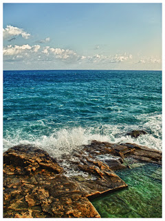 A rocky beach with waves in Kalkara, Malta
